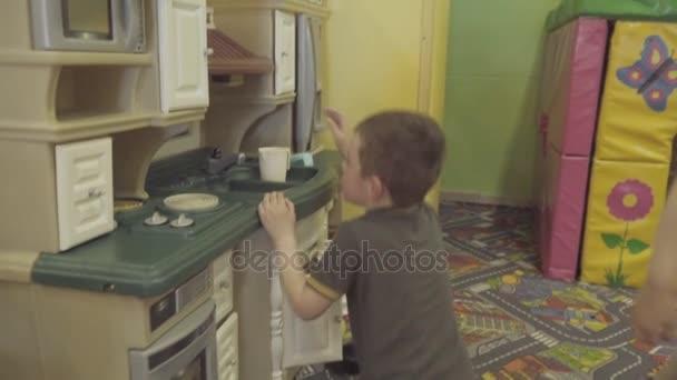 děti hrají s malými kuchyňského nábytku