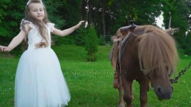 The girl is walking next to the pony