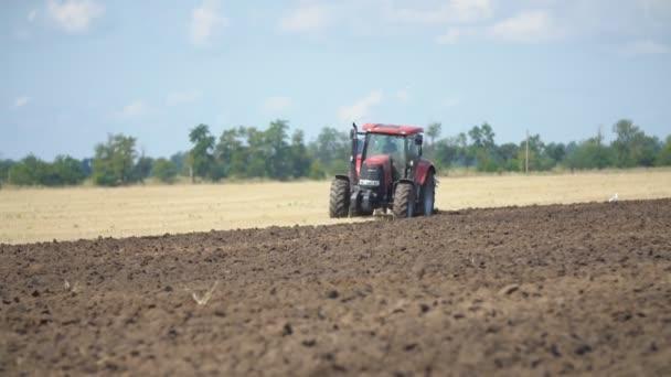 červený traktor orá pole