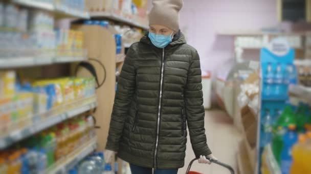 orvosi maszkos nő sétál sorok között egy szupermarketben