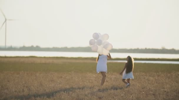 Mutter mit Tochter und Luftballons wandern in der Natur