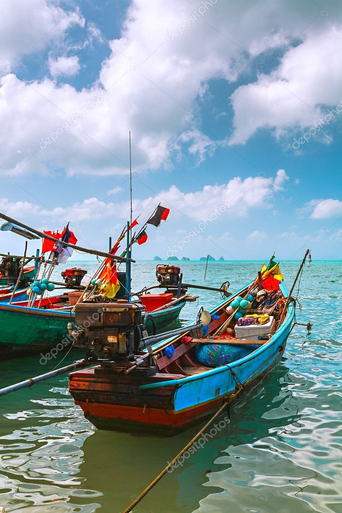 Colored fishing boats in the sea on the turquoise wave