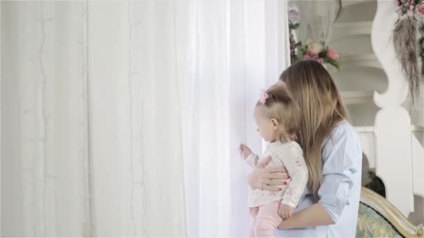 Mother With Her Little Baby Girl Standing Near The Window And Looking Outside
