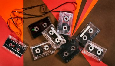 Vintage music cassette tape on retro background. Flat retro lay. 70's, 80's, 90's old school record technology poster.
