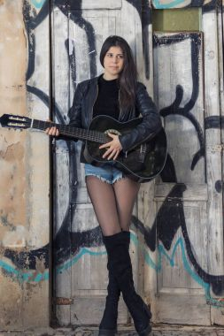 Close view of a beautiful young woman with classic guitar on the street of the city.