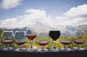 Pět sklenky koňaku a dvě sklenice červené a růžové víno stojan na pozadí krásné horské krajiny a lanovky. Existují bílé mraky na modré obloze.