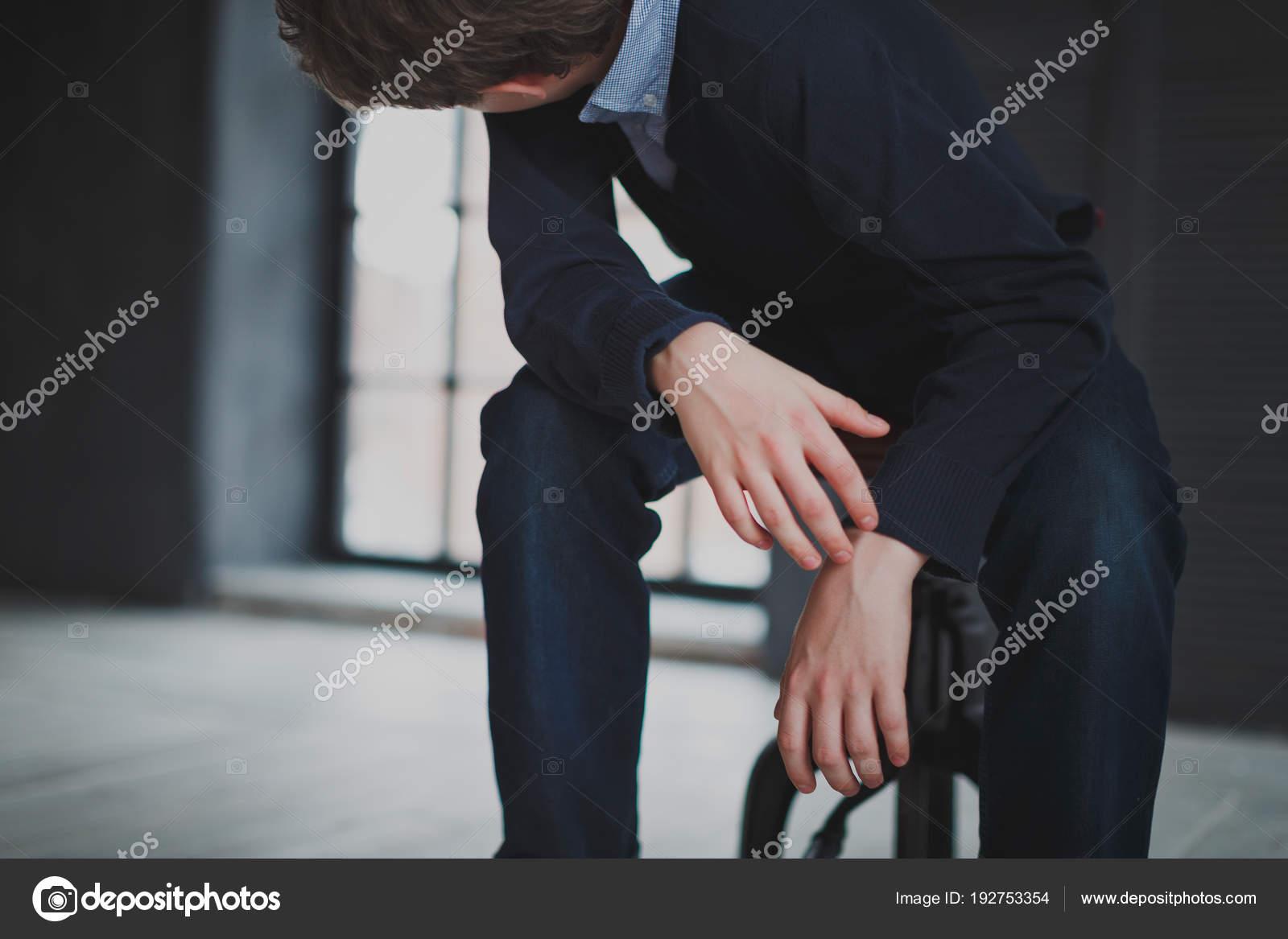 Triest broeden tiener jongen blauwe vrijetijdskleding zit een stoel