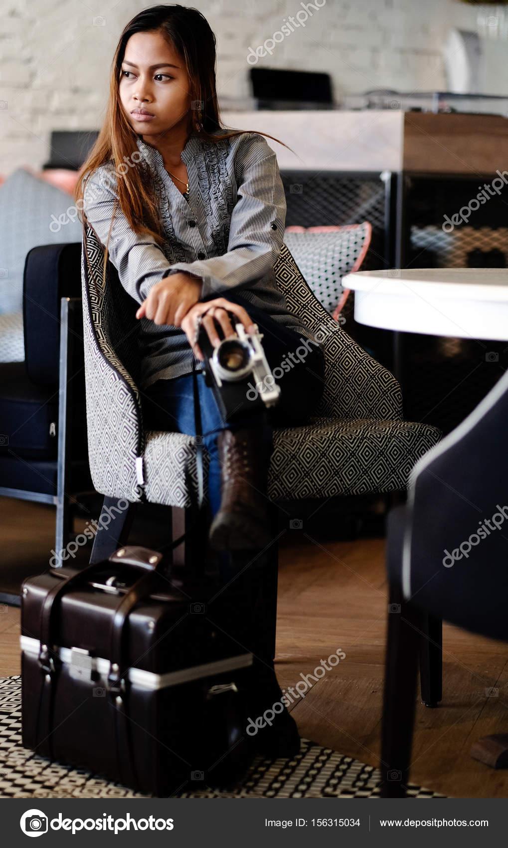 9d88b0479 Hermosa niña sentada en un bar con antiguo vintage Retro cámara en sus  manos. Moda joven mujer sentada en un bar — Foto de ...