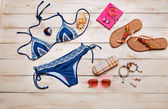 Flat lay of summer fashion with blue bikini swimsuit, and girl accessories on white wooden  background