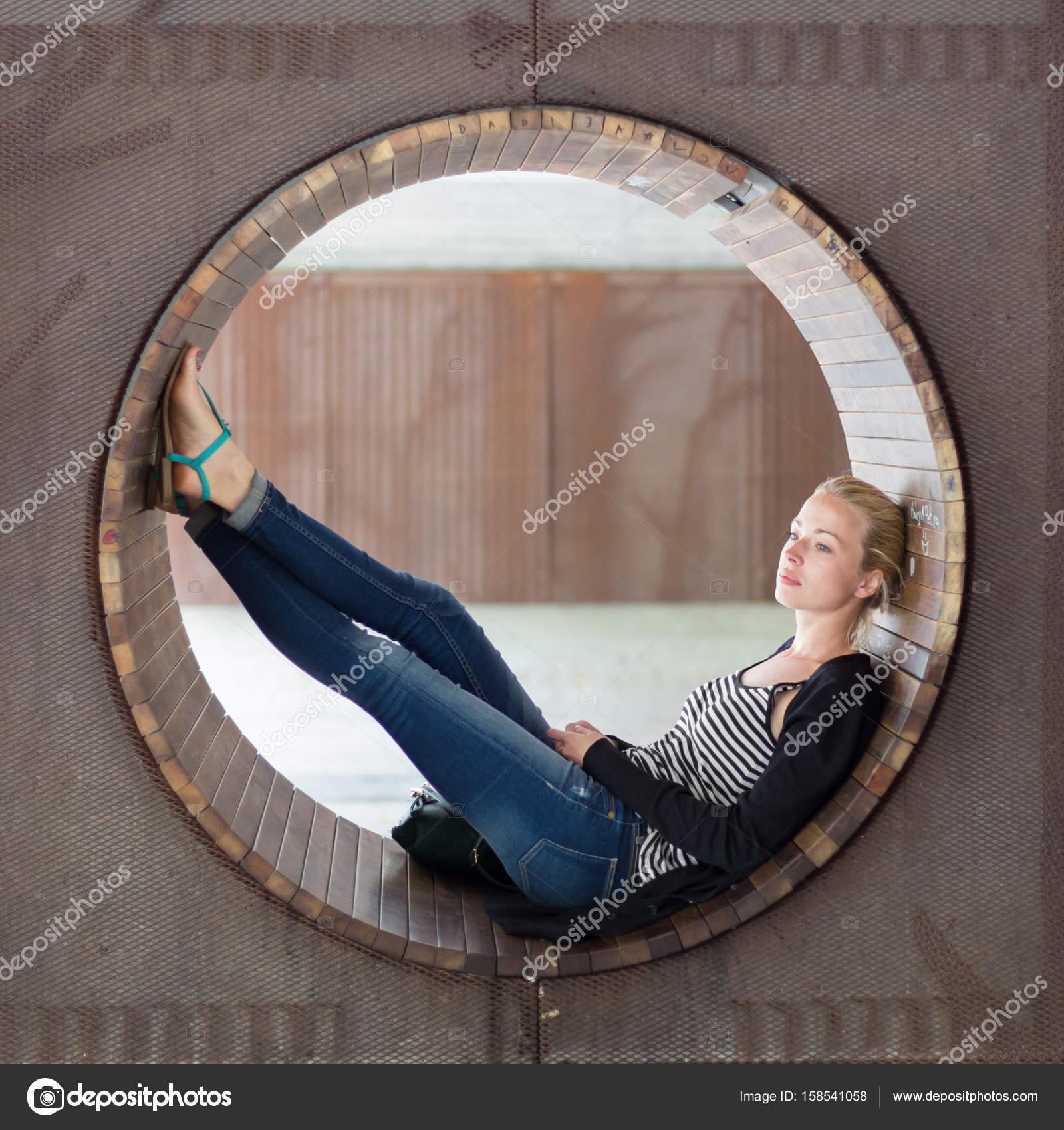 Junge nachdenkliche Frau entspannend auf Bank im Stadtpark ...