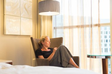 Businesswoman on business travel, tired from business meeting, sitting alone in hotel room afterwork, reading and responding to emails and messages on her smart phone