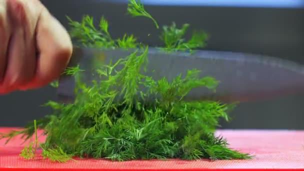 Nakrájená zelenina. Šéfkuchař Cutting Dill. Šéfkuchař stříhá Dill Greens zpomaleně. Jídlo z blízka. Proces vaření. Kuchařská mísa. Šéfkuchař připravuje jídlo. (Red Dragon Camera, Cinematic Quality Macro Footage).