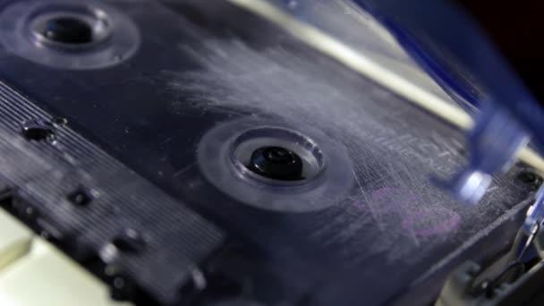 Audio kazeta v magnetofonu přehrává a otáčí. Detailní záběr. Klasická transparentní kazeta použitá pro nahrávání nebo přehrávání zvuku na retro kazetovém přehrávači.