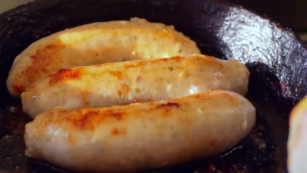 Hot dog nyers kolbász sistereg és főzni egy régi öntött serpenyőben