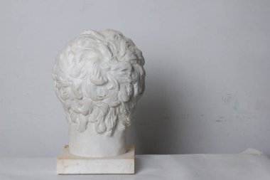 classical plaster head bust against a white, old, worn wall. rear view Artist's studio