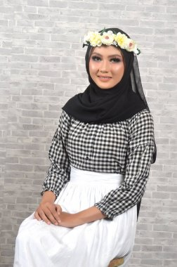 Portrait Beautiful Muslim Asian Girls with a checkered motif, a hijab with flower headbands, a photo in a studio with a gray brick background