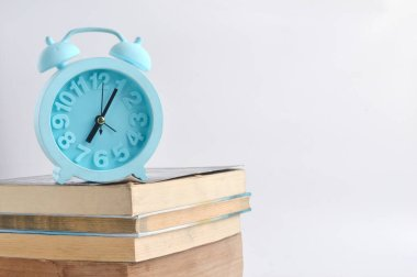 stack of books and a blue alarm clock on white background