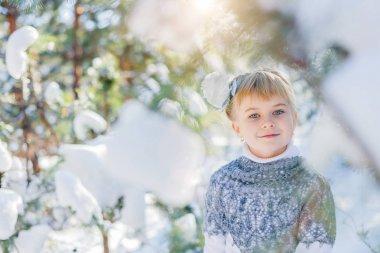 Winter fairy tale. Beautiful little girl is walking in a snowy forest