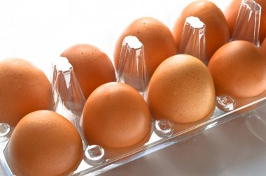Fresh organic brown eggs in a plastic box package, isolated on white background