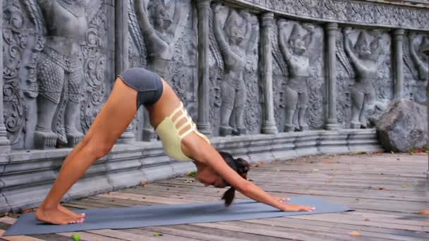 Asian young woman doing hatha yoga in abandoned temple