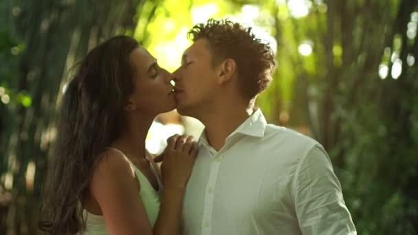 Láska, pár líbání. Zblízka romantický pár polibek v lese zelený bambus