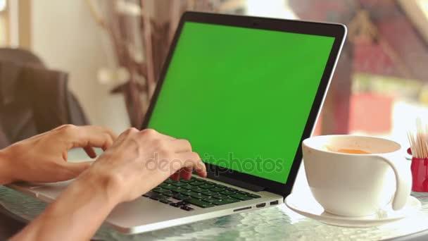 Közeli kép a férfi kezét használ laptop kávézóban zöld képernyő