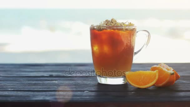 Glass of ice tea with hrysanthemums and orange, ice cubes on dark wooden table