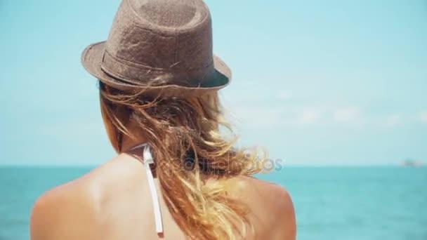 Gyönyörű nő a strandon nézi horizonton lassított