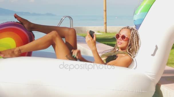 Atraktivní žena ležící na nafukovací jednorožec a používání smartphone