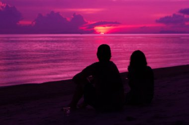 Silhouette of the couple on the beach on sunset