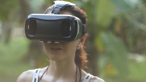 woman uses a virtual reality glasses in the jungle in slow motion, orbit shot