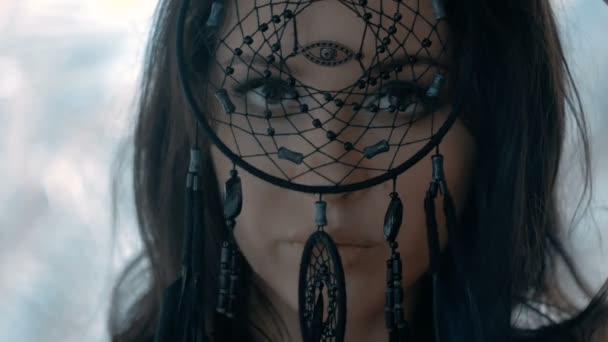 Mysterious sexy woman with make up looking through black dream catcher