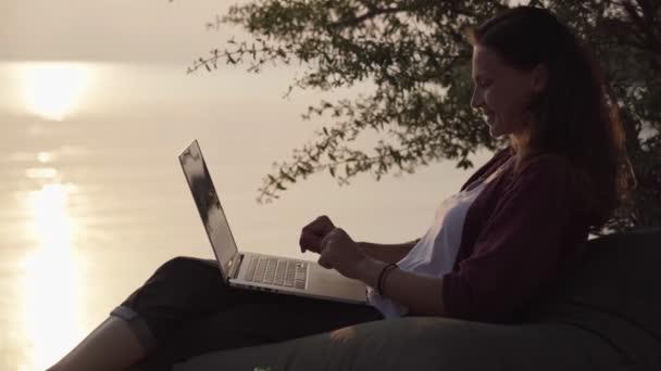 Mädchen arbeitet mit Laptop am tropischen Strand