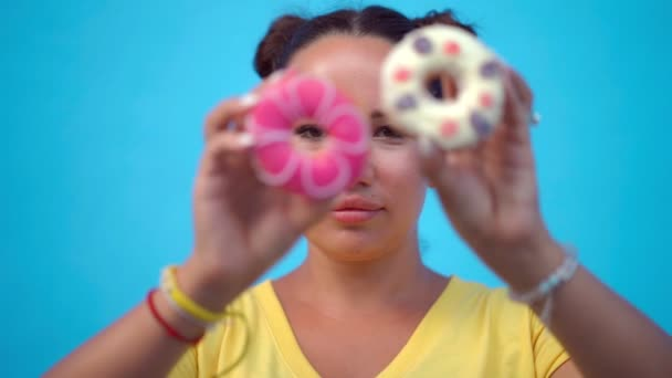 Woman covering her eyes with donuts