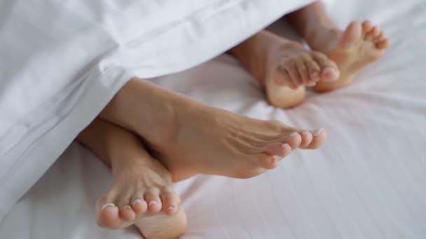 Szoros a női pár játszani és táncolni a lábukat takaró alatt, miközben felébrednek az ágyban reggel