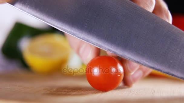 cuts red tomato among the fresh vegetables. Vegetables table- top