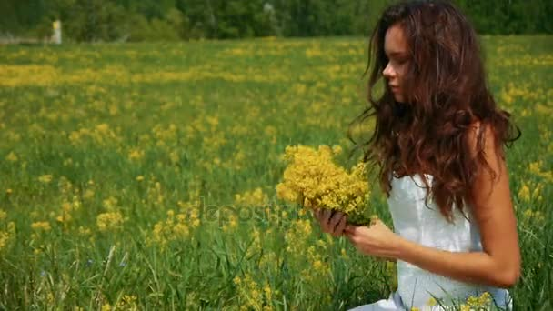 Beautiful woman breathes yellow flowers in a green field