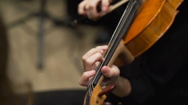 Violoncellist játszik a zenekar a színpadon konzervatóriumban. Közelről