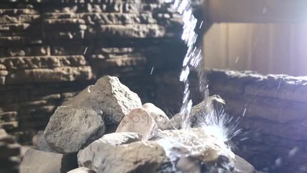 Voda teče na kameni v sauně. Koncepce zdraví. Zpomalený pohyb. Detail