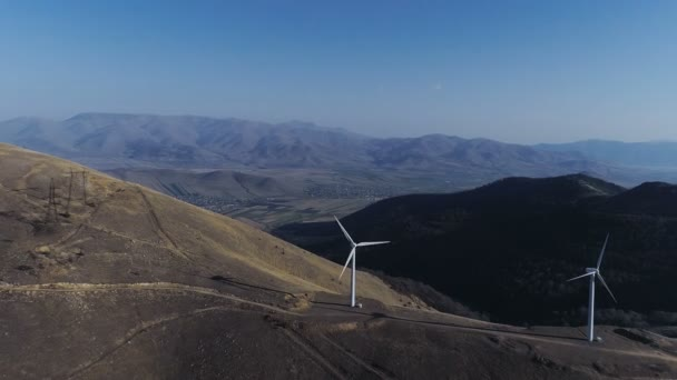 Wind turbines create renewable energy Cooling tower of power plant in background