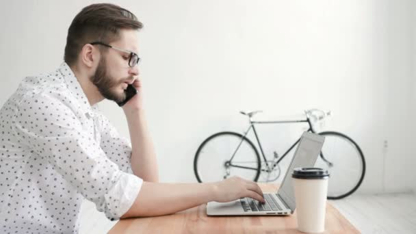 Man in office talking at phone and type at laptop