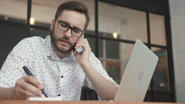 Man talking at smartphone and writing in office