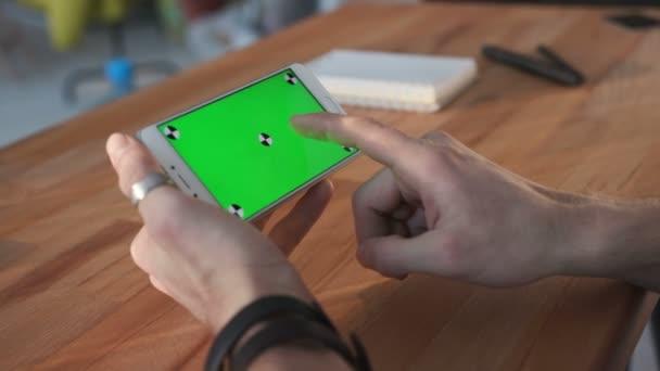 Ember használ smartphone zöld képernyős asztalnál