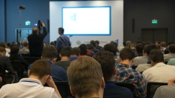 Lidé sedí na konferenci hlediště s obrazovkou a čeká na