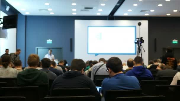 Menschen sitzen im Konferenzsaal mit Bildschirm und warten auf