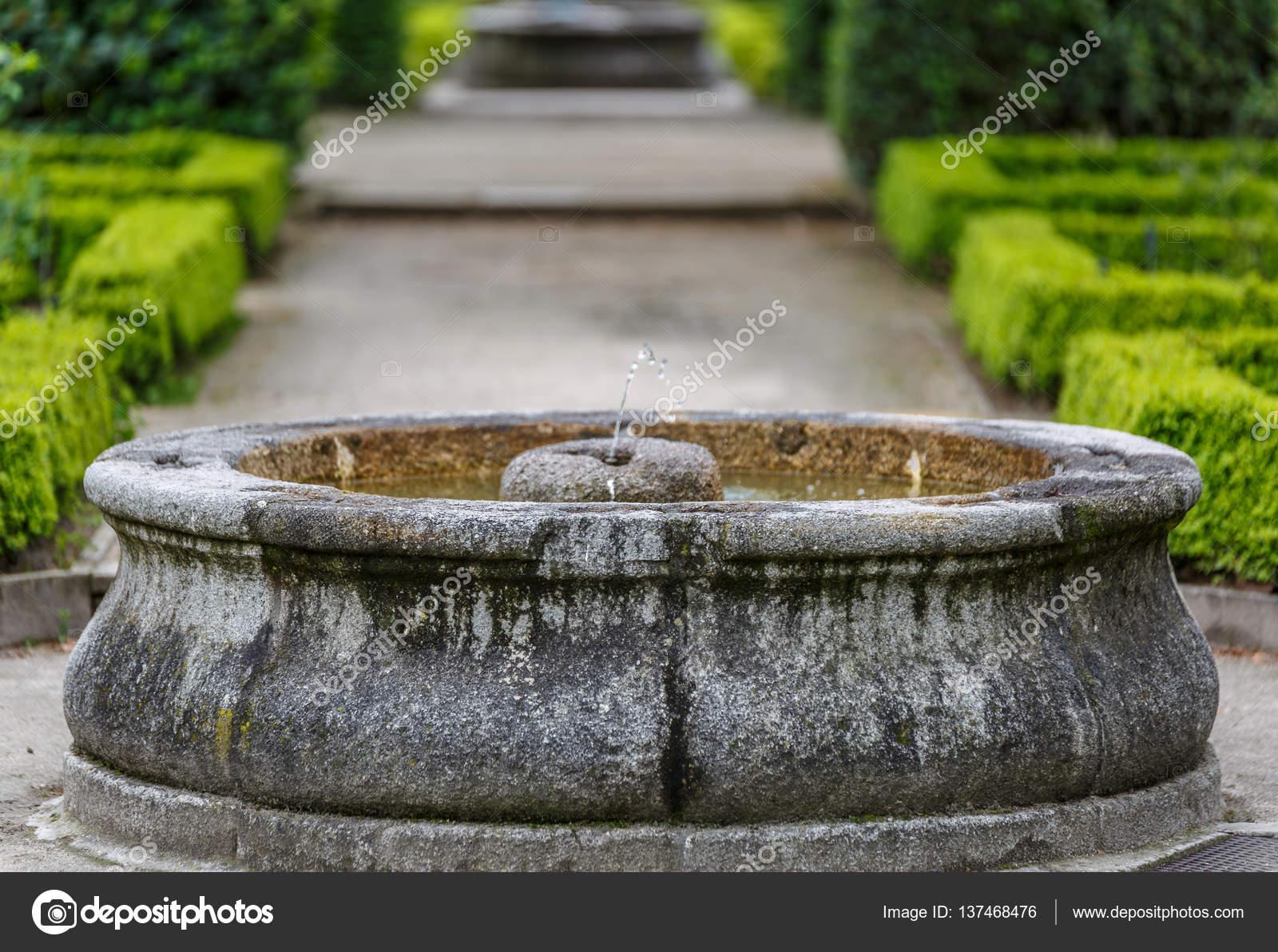 Stein-Wasser-Brunnen in der Mitte einen hübschen Garten — Stockfoto ...