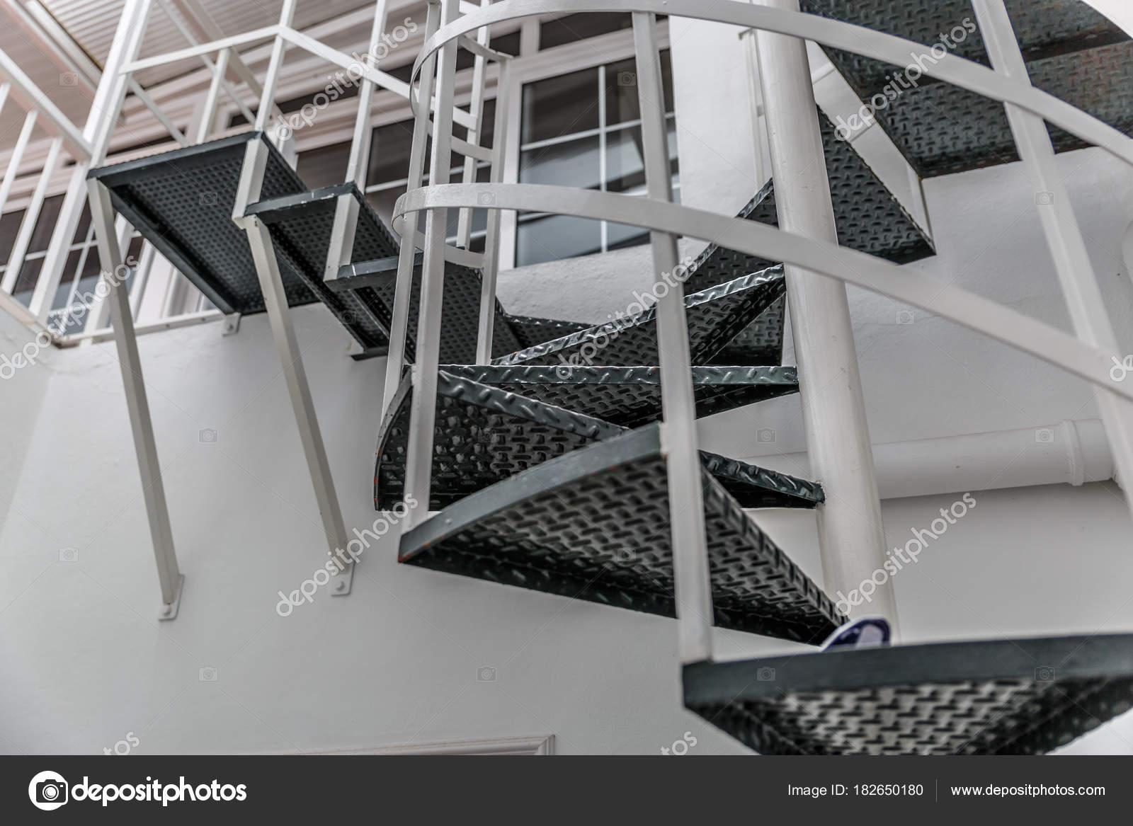 Vista desde abajo de una escalera de caracol metálica con pasos ...