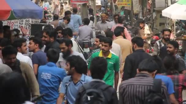 LAHORE, PAKISTAN - MAY 05, 2015: Pedestrians rush and traffic move along Mobile Market Hall Road on May 05, 2015 in Lahore, Pakistan.