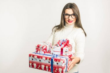 Portrait of a beautiful woman in white sweater and glasses with shopping bags (Gift). On a white background. Mock up. Human. New Year. Christmas. Birthday. Thanksgiving Day. Mothers Day
