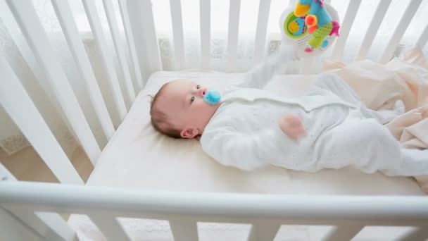 Dolly záběr roztomilé 3 měsíce starý chlapeček ležel v bílé dřevěné postýlce s hračkou kolotoč